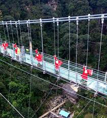 Dancers in ancient-style costumes perform on a glass bridge in Fujian